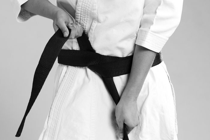 femme qui noue sa ceinture noire sur un kimono